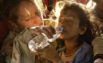 Femme qui donne de l'eau a un enfant